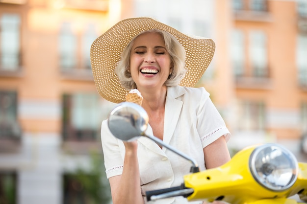 Woman with ice cream laughing.