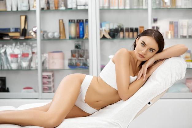 치료 절차 후 스파 살롱에서 착용 아래에 누워 이상적인 그림을 가진 여자
