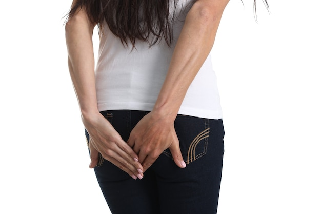 Woman with indigestion stands with back holding hand on butt