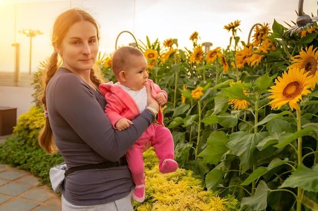 Женщина с младенцем, наслаждаясь восходом солнца в саду подсолнухов, держа ребенка на руках