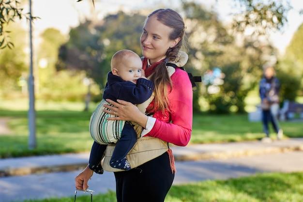 Женщина с младенцем в слинге стоит в общественном парке