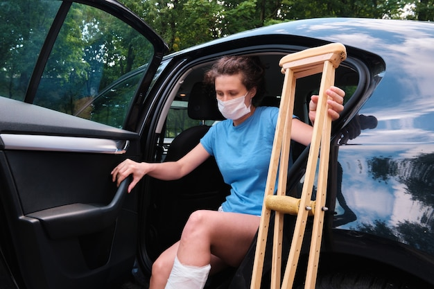 A woman with an injured leg gets into a car orthopedic plaster orthopedic crutches