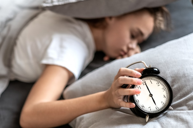 Woman with insomnia lying in bed with her head under her pillow trying to sleep.