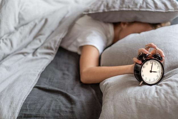 眠ろうとする彼女の枕の下で彼女の頭でベッドに横たわっている不眠症の女性。不眠症と睡眠障害。