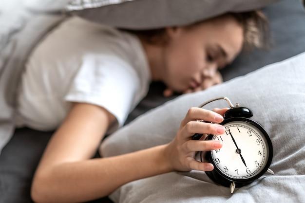 眠ろうとしている枕の下に頭を抱えてベッドに横たわっている不眠症の女性。