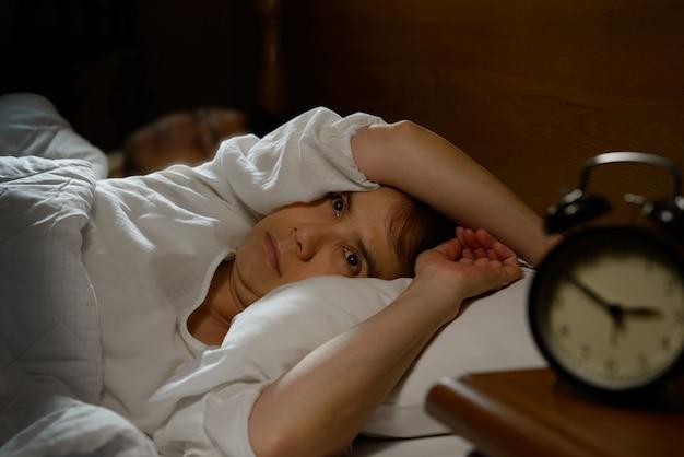 열린 눈으로 침대에 누워 불면증을 가진 여자