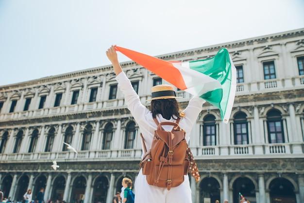 여름 시간 세인트 마크 광장 뒤에서 이탈리아 국기 보기를 가진 여자