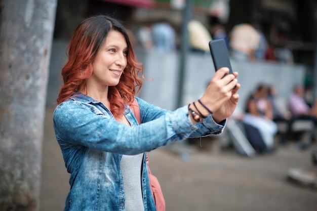 Женщина в джинсовой куртке фотографирует