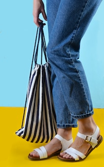 A woman with jeans and sandals is holding a beach striped bag on a blue wall. summer time in a sea resort
