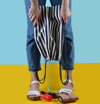 Woman with jeans and sandals is holding a beach striped bag on a blue yellow wall. women's accessories  falling out of the bag. what's in the women's bag? summer time in sea resort