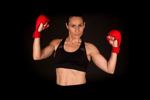 Женщина с перчатками каратэ на черном фоне