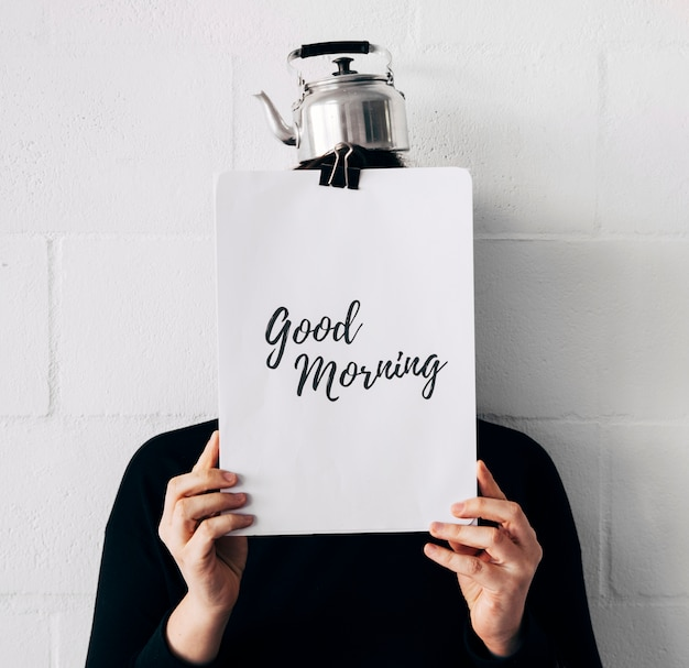 흰 벽에 얼굴 앞에서 들고 종이에 머리와 좋은 아침 메시지 주전자와 여자