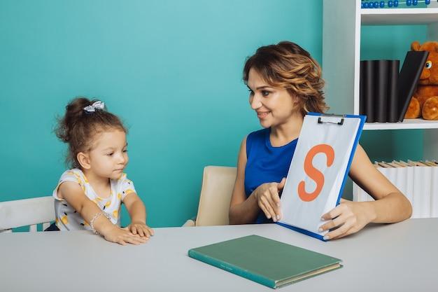 白い部屋に座って一緒にスピーチを訓練する子供の女の子を持つ女性。