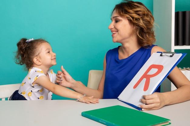 白い部屋に座って一緒にスピーチを訓練する子供の女の子を持つ女性