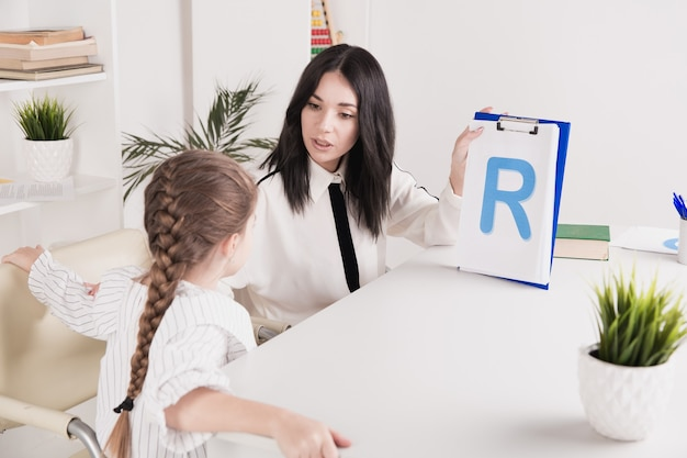Woman with kid girl training speech together sitting in the white room.