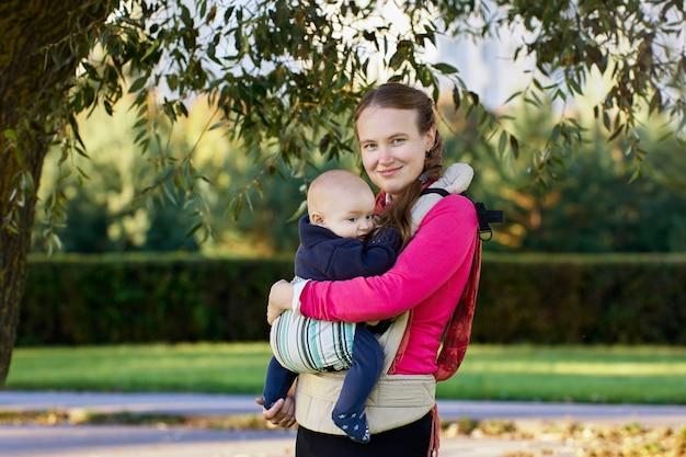Женщина с ребенком в слинге гуляет на открытом воздухе в летний день