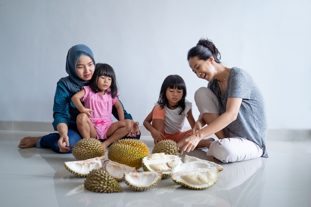 Woman with kids eating durian fruit