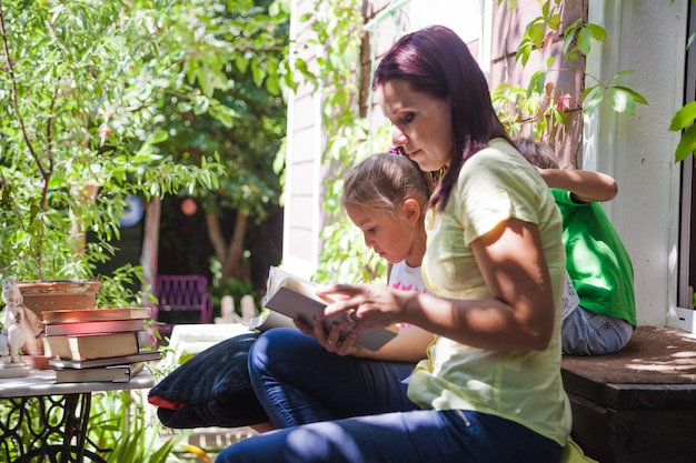 ポーチで子供たちが読書をする女性