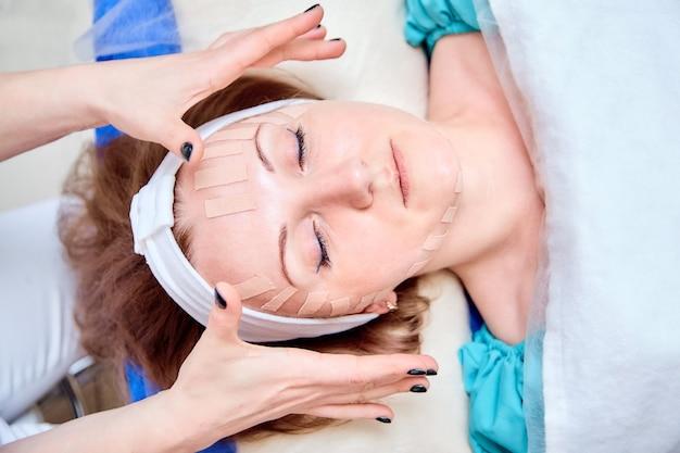 顔にキネシオロジーテープを持つ女性