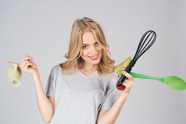 灰色の背景の感情にキッチン家電を持つ女性モデル主婦トリミングビュー