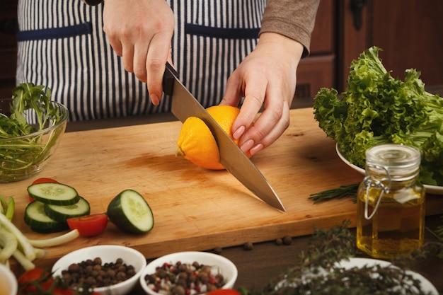 木の板にレモンを切るナイフを持つ女性。新鮮な夏のサラダの準備、健康的な食事のコンセプト、側面図、コピースペース