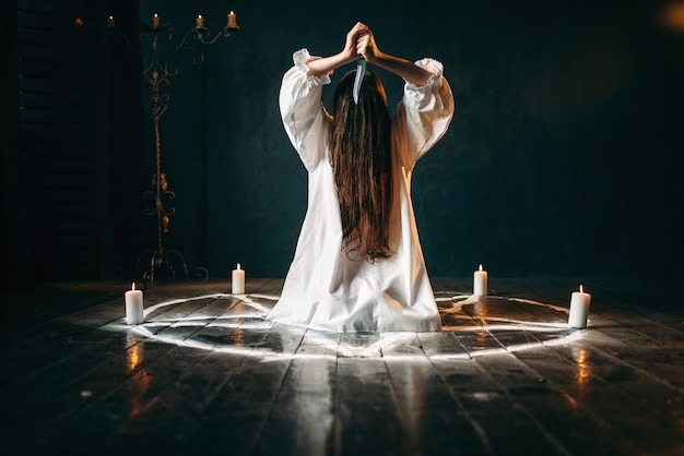 Woman with knife in hands sitting in pentagram circle with candles. dark magic ritual, occultism and exorcism, supernatural power