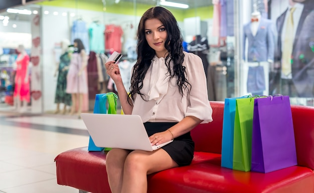 노트북 및 쇼핑몰에서 신용 카드를 가진 여자