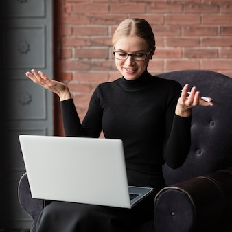 ノートパソコンとソファの上の電話を持つ女性