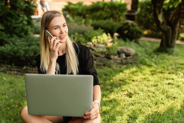 Женщина с ноутбуком и смартфоном на открытом воздухе.