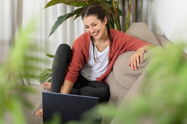自宅でラップトップを持つ女性