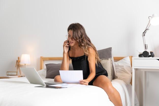 Donna con il computer portatile sul letto parlando al telefono