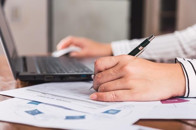 ペンで作業し、書いているラップトップコンピューターを持つ女性。