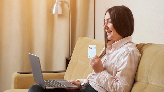 ノートパソコンを持っている女性は、英語のアルファベットの文字でポストカードを示し、音や単語を発音します。
