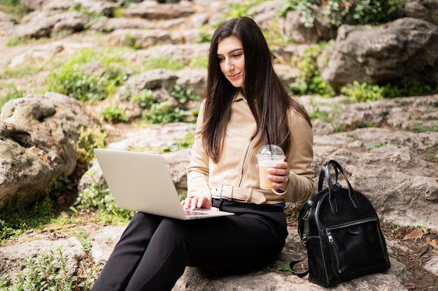 Woman with laptop and drink working outdoors