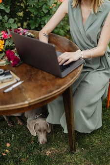 Woman with a laptop in the garden working with her dog