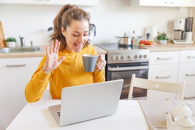 Женщина с ноутбуком, имеющая виртуальную встречу, чат, видеоконференцию, сидя на кухне дома