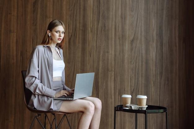Женщина с ноутбуком в наушниках с кофе сидит, глядя на фронт