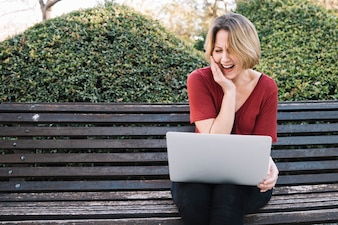 Woman with laptop laughing