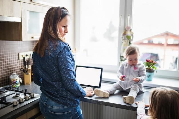 キッチンで彼女の子供を見てラップトップを持つ女性