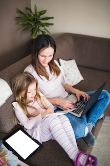 Woman with laptop looking at her daughter studying