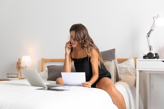 電話で話しているベッドの上のラップトップを持つ女性