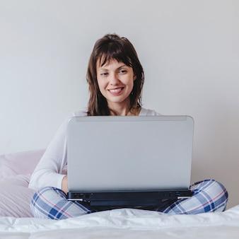 ベッドに座っているラップトップでラップトップを持つ女性