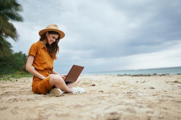 砂浜のラップトップを持つ女性