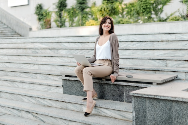 Woman with laptop outdoor on the stairs