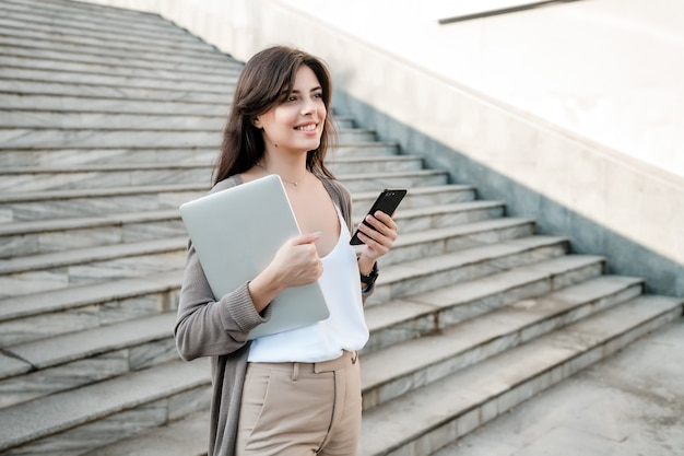 Woman with laptop and phone in the city