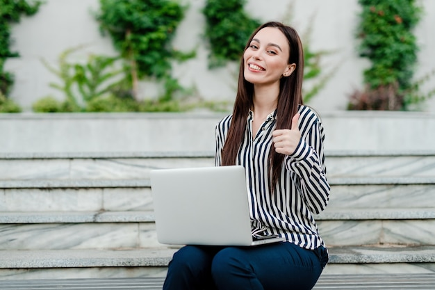Woman with laptop shows thumbs up
