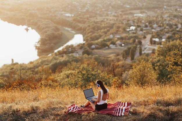 노트북을 가진 여자 강과 마을 언덕에 앉아있다.