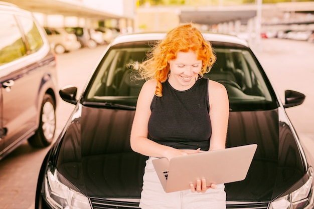 Woman with laptop sitting on hood of car