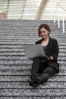 Woman with laptop sitting on stairs