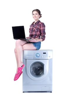 Woman with laptop sitting on the washing machine.
